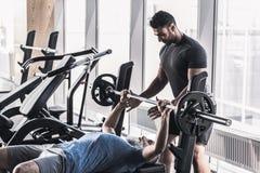 Mâle supérieur faisant des exercices avec son entraîneur au centre sportif photo stock