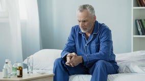 Mâle supérieur malade bouleversé s'asseyant sur le lit, prenant le médicament pour récupérer de la maladie Image libre de droits