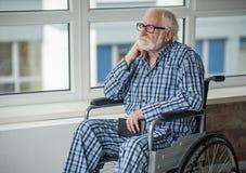 Mâle supérieur triste s'asseyant dans le fauteuil roulant dans la chambre Photos stock