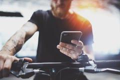 Mâle tatoué barbu dans des lunettes de soleil utilisant le smartphone après la monte en le scooter électrique dans la ville photo libre de droits
