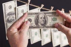 Mâle tenant cent billets d'un dollar, beaucoup remettant de la corde à linge Image libre de droits
