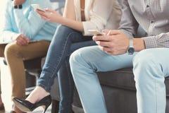 Mâles jeunes et dame attendant dans la file d'attente l'entrevue d'emploi Image stock