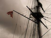Mât sur le vieux schooner avec le vol de drapeau dans le vent un jour pluvieux Photographie stock