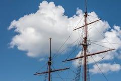 Mâtez le bateau de navigation sur un fond des nuages Images stock