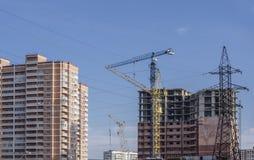 Mâts à haute tension parmi de nouveaux bâtiments Photo stock
