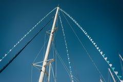 Mâts de yacht à l'arrière-plan de ciel bleu Image libre de droits