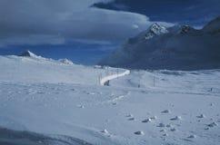 Mäanders van Rhätische Railyway in de diepe sneeuw van de Zwitserse alpen bij Bernina-Pas royalty-vrije stock afbeeldingen