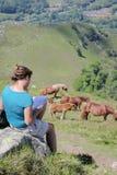 Mädchen, das eine Karte und Pferde auf dem Hügel über der Stadt von Lourdes liest jpg lizenzfreie stockfotos
