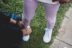 Mädchen, das ihre Spitzee von ihrer Mutter binden lässt stockfoto