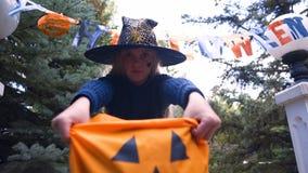 Mädchen, das Süßes sonst gibt's Saures Tasche, fordernde Bonbons am Parteieingang, Halloween hält lizenzfreies stockfoto