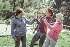 Mädchen in den sportiven Uniformen, die fünf geben lizenzfreie stockfotografie