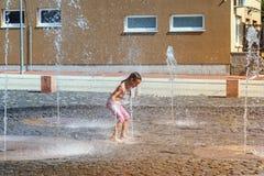 Mädchen an einem sonnigen warmen Tag, der draußen in einem Wasserbrunnen spielt Mädchen glücklich im seichten Trinkwasser an des  lizenzfreie stockbilder
