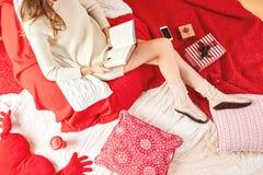 Mädchen kleidete Strickkleid und gestrickte Sockenlügen und liest ein Buch auf rot-weißen Decken und Kissen mit, rote Schale von stockfoto
