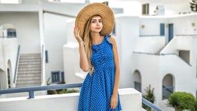 Mädchenblondine mit dem langen Haar in einem Strohhut in einem blauen Kleid mit Tupfen steht in Santorini stockfotos