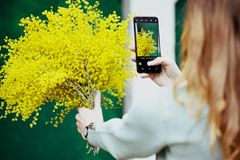 Mädchenphotographien ihr Blumenstrauß am Telefon, Bild, Technologie, Feiertag lizenzfreie stockfotografie