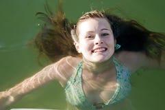 Mädchenschwimmen des jungen jugendlich im Wasser Stockbilder