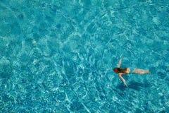 Mädchenschwimmen Unterwasser in einem Pool draußen lizenzfreie stockbilder