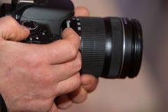 Männliche Hände, die einen digitalen SLR-Kameraabschluß hochhalten stockbilder