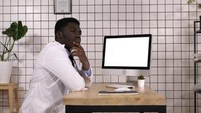 Männlicher hübscher afrikanischer Doktor, der nahe bei seinem Computer denkt Weiße Bildschirmanzeige lizenzfreie stockbilder