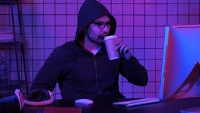 Männlicher mit Kapuze Gamer, der ein Spiel auf Computer aufpasst stockbilder