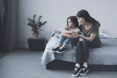 A mãe abraça sua filha, que se senta ao lado dela na cama com seus braços em torno de seus pés e se faz uma carranca lateralmente Imagem de Stock