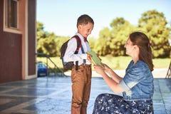 A mãe acompanha a criança à escola a mamã incentiva o estudante que acompanha o à escola uma mãe de inquietação olha maciamente n fotos de stock
