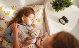 A mãe acorda sua filha na cama na manhã Imagem de Stock