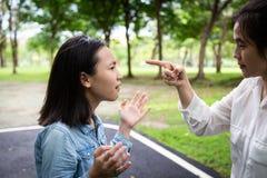 Mãe adulta irritada do retrato do close up que discute, discutindo com a filha nova no parque exterior, o pai e a gritaria asiáti foto de stock royalty free