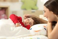 Mãe afetuosa que olha seu sono da criança imagens de stock