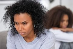 Mãe afro-americano irritada virada que ignora a filha após a discussão foto de stock