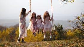 A mãe agita suas filhas em um balanço sob uma árvore filme