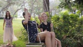 A mãe agita suas filhas em um balanço sob uma árvore video estoque
