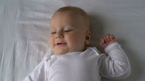 A mãe agrada o bebê e ri o encontro na cama video estoque