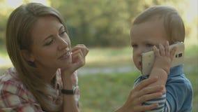 A mãe ajuda o filho pequeno a chamar seu pai com video estoque