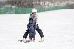 A mãe ajuda o menino Ski Downhill da criança Vestido com segurança com capacete imagens de stock royalty free