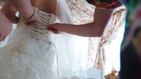 A mãe ajuda sua filha a prender o laço no garnment da fundação video estoque