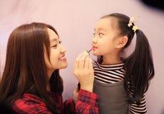A mãe ajudou sua filha a compor e manchar o batom Foto de Stock Royalty Free