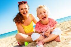 Mãe alegre e criança modernas que sentam-se na praia imagem de stock royalty free
