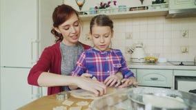 A mãe alegre e a filha bonito pequena que falam e que fazem as cookies que usam junto a padaria formarem a massa da colheita quan filme