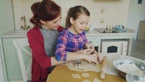 A mãe alegre e a filha pequena que fazem as cookies que usam junto a padaria formam a massa da colheita ao sentar-se em moderno vídeos de arquivo