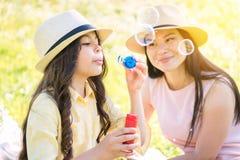 Mãe alegre e filha que têm o divertimento na pastagem fotografia de stock