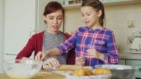 Mãe alegre que cozinha na cozinha quando mamã de vinda e de abraço da filha bonito na manhã Família, alimento, casa vídeos de arquivo