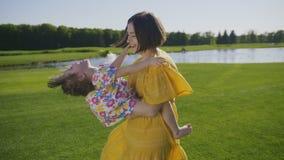 Mãe alegre que gira a menina speial das necessidades no parque filme