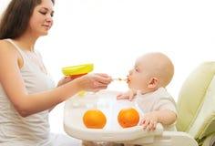 A mãe alimenta a colher do bebê na casa da tabela Imagem de Stock