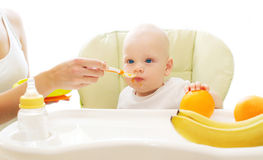 A mãe alimenta a colher do bebê na casa da tabela Imagens de Stock Royalty Free