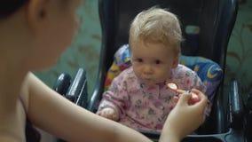 A mãe alimenta a criança com papa de aveia vídeos de arquivo