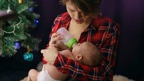 A mãe alimenta a filha recém-nascida Natal fotografia de stock