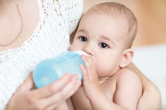 A mãe alimenta o leite do bebê da garrafa Imagem de Stock
