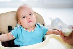 A mãe alimenta sua casa de nove meses do leite do bebê Foto de Stock