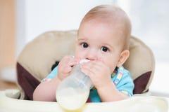 A mãe alimenta sua casa de nove meses do leite do bebê Fotografia de Stock Royalty Free